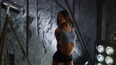 чувственность : Slim beautiful woman with inflated press in black short shorts and gray top on stone wall background. stretches the muscles before training