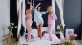 yatak kıyafeti : Pajama party before the wedding three bridesmaids dance on the bed laughing and looking at the camera