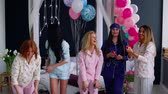 yatak kıyafeti : A group of girls laughing and smiling in pajamas launching confetti in slow motion 120 frames per second. Toss airbags shiny candies at a party