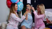 yatak kıyafeti : The bridesmaids sitting in a circle bumping glasses with champagne wishes and say happy for the impending marriage. Congratulations on the happy event. Womens pre-wedding party. Laughter and joy. Bridesmaid. Pajama party Stok Video