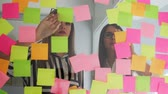 memorando : Creative business team brainstorming ideas working together sharing data late at night after hours in modern glass office. Two very beautiful girls in office clothes blonde and brunette with glasses look at the colored stickers and offer ideas Vídeos