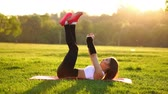 абс : Woman doing abdominal crunches exercise on the fitness mat in summer park In slow motion at sunset. Стоковые видеозаписи