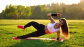 chroupat : Woman doing abdominal crunches exercise on the fitness mat in summer park In slow motion at sunset. Dostupné videozáznamy