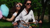 electric scooters : Two young and sexy arson brunette with loose hair in short denim shorts and white shirts go on an electric motorcycle in the Park, enjoying hugging each other Stock Footage