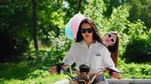 electric scooters : Two young and sexy brunette friends with loose hair in short denim shorts riding an electric motorcycle in the Park on a Sunny day enjoying hugging each other. Best friends spend time together Stock Footage