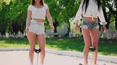 electric scooters : Two sexy young girls riding on hoverboard in short shorts holding hands and laughing on a Sunny day in the Park Stock Footage