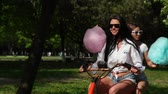 electric scooters : Two young sexy brunettes with loose hair in short denim shorts and white t-shirts go on an electric motorcycle in the Park laughing and smiling with sweet cotton