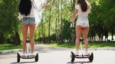 lambreta : Two girlfriends riding on white hoverboard launch soap bubbles Stock Footage