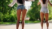 orientar : Two girls in short shorts ride from the rear view camera on a self-balancing scooter in the Park