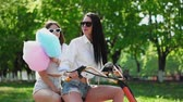 lambreta : Two beautiful girls in denim shorts ride in the Park on an electric scooter in the summer Vídeos