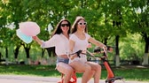electric scooters : Sexy girls with sweet cotton in short shorts ride an electric scooter in the Park