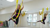 denge : Young beautiful woman doing aerial yoga practice in purple hammock in fitness club.