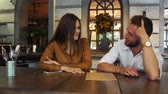 dark haired : Nice couple are sitting together in a restaurant. She is drinking some tea and looking to a menu while her biyfriend is trying to pick food for them. Also he is giving food advices to her. Stock Footage
