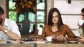 compartilhando : Multi-ethnic group of young friends talking and using smartphones apps on wifi in cafe, happy millennial people having fun with phones sharing coffee house table enjoying meeting in public place
