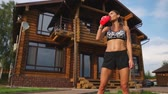 марафон : Crooked brunette with inflated press muscles and black shorts, drinking protein after a workout on the street against the background of a huge house with large Windows Стоковые видеозаписи