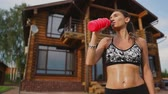 konak : Crooked brunette with inflated press muscles and black shorts, drinking protein after a workout on the street against the background of a huge house with large Windows Stok Video