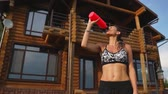 abdominaux : Sporty brunette woman with nice abs in black top is wet from sweat on the background of wooden mansion after a workout, drinks water from a bottle