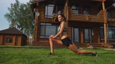 konak : A slim and beautiful woman in sportswear with an open press is preparing to start training on the lawn near her home flexing her legs, knees, shins and thighs with warming up exercises Stok Video