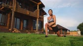 coxa : A slim and beautiful woman in sportswear with an open press is preparing to start training on the lawn near her home flexing her legs, knees, shins and thighs with warming up exercises Vídeos
