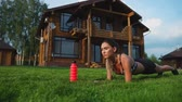 workout : beautiful brunette on the background of a large mansion engaged in fitness and performs plank exercise for the press Stock Footage