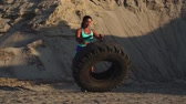 kolano : Girl in sportswear pussh a tire. Street workout. Wideo