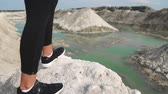 halter : Sporty brunette girl in black sportswear trains against a white chalk sand quarry with blue water. Close-up of feet in sneakers fit to the edge of the mountain overlooking the blue river.