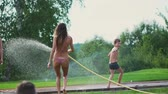 hadice : Mom with two kids playing with garden hose pouring water on the grass