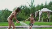 postřikovačů : Mom and son playing on the lawn pouring water laughing and having fun on the Playground with a lawn on the background of his house near the lake