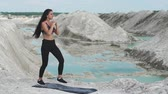 energy body : Sporty brunette girl in black sportswear trains against a white chalk sand quarry with blue water. Lunges on each leg for thighs