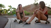 um jovem mulher só : Two girlfriends communicate in the Park sitting on skateboards laughing and smiling Vídeos