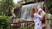 wozek dzieciecy : Traveling with a child, a young mother plays and hugs her son near the waterfall. Kisses baby on the cheek Wideo