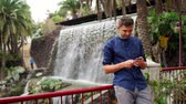 monumentální : Handsome young businessman outdoors, sliding smartphone touchscreen, waterfall