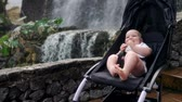 inocência : The baby sits in a wheelchair near the waterfall and laughs looking at the camera in the remsa travel with parents on the Canary Islands.