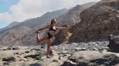 шпагат : Young woman in bodysuit practicing yoga on the beach above sea at amazing sunrise. Fitness, sport, yoga and healthy lifestyle concept. Girl doing one leg stand and twine