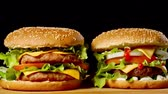 susam : Close-up of two appetizing burgers with sesame buns rotating on black background, of fast food seamless looping shot . Stok Video