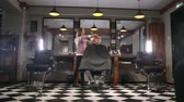 kuaför : Interior shot of working process in modern barbershop. Side view portrait of attractive young man getting trendy haircut. Male hairdresser serving client, making haircut using metal scissors and comb.