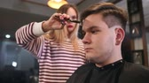 Interior shot of working process in modern barbershop. Side view portrait of attractive young man getting trendy haircut. Male hairdresser serving client, making haircut using metal scissors and comb.