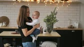 Mom hugs the baby and the child smiles looking at his beloved mother. Together stand in the white kitchen on Christmas eve on the background of garlands and Christmas trees. Happy Mother and Baby kissing and hugging.Maternity concept Motherhood Beautiful