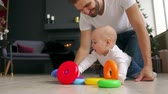 family, fatherhood and people concept - happy father with little baby son playing with toys at home Dostupné videozáznamy