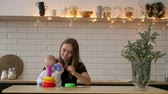 Toddler with mom playing with the toy in nursery room. Mother with her 1 year-old baby boy having fun at home
