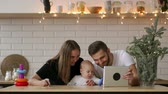 family, parenthood and people concept - happy mother and father showing tablet pc computer to baby at home Dostupné videozáznamy