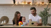 family of mother, father and baby sitting at home with a tablet PC Стоковые видеозаписи