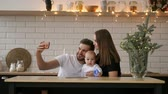 family, parenthood, technology and people concept - happy mother, father and little boy having dinner and taking selfie by smartphone at restaurant
