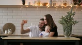 family, parenthood and people concept - happy mother and father with baby taking selfie at home Стоковые видеозаписи