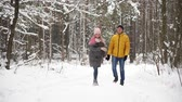 wintertime : A man in a yellow jacket and a girl in a hat and scarf walk through the winter forest during a snowfall laughing and smiling at each other at Christmas in slow motion