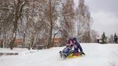 rubber tubing : Dad pushes her daughter on a rubber inflatable snow tube in slow motion