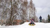 rury : Happy mom and daughter sledding in winter in snow and playing snowballs. mother and child laugh and rejoice glide on an inflatable tube. Family playing park during Christmas holidays. Slow motion