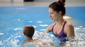 mateřský : Cute baby boy enjoying with his mother in the pool.