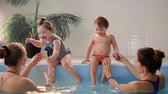suckling : Two babies laugh in the pool and jump into the water clapping their hands