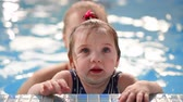 offspring : Little baby girl while swimming in the pool looking at the camera standing on the side in the water and smiling Stock Footage